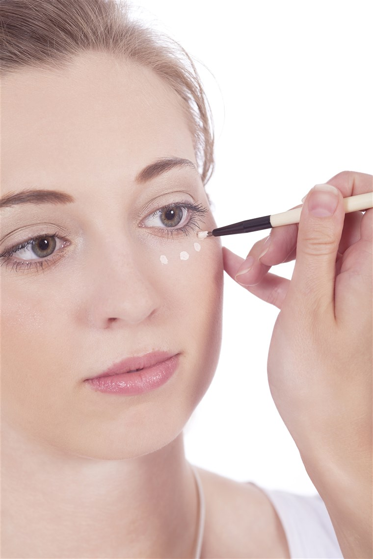 kobieta applying concealer