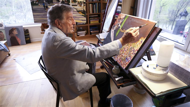 W his New York art studio, Tony Bennett finishes a painting while sitting among several of his completed works.