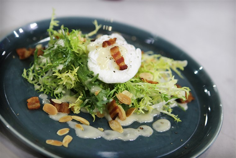 Gepocheerd eggs, frisee salad with bacon lardon, toasted almonds and Dijon vinaigrette