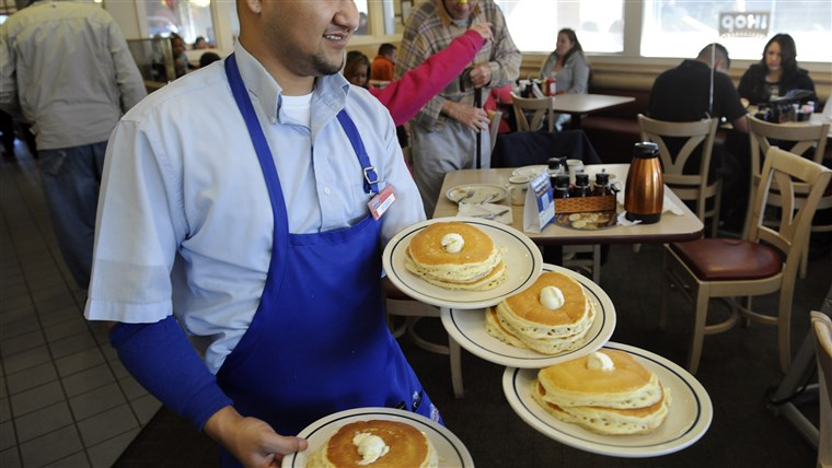 Servidor Ruben Avalos performs a balancing act with several plates of the free pancakes.