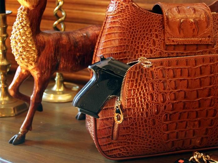 Dette crocodile-print leather hobo has a discreet compartment specially designed to conceal a firearm