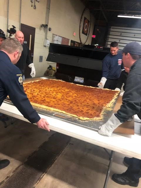 Mallie's Grill and Bar, Southgate, MI, delivers largest commercially available pizza to local fire department.